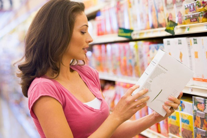 woman checking food labels to read portion sizes