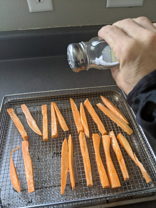 shaking salt on sweet potatoes for the air fryer