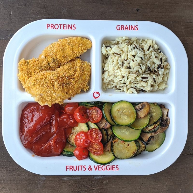 Chicken tenders rice and zucchini on a portion plate