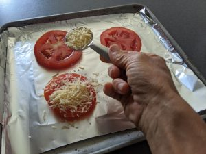 sprinkling cheese on tomatoes