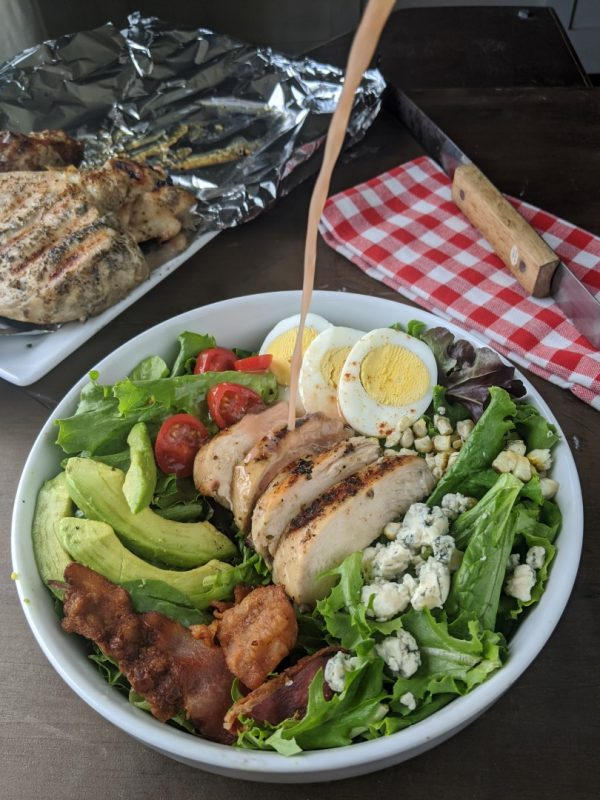 pouring dressing on grilled chicken cobb salad